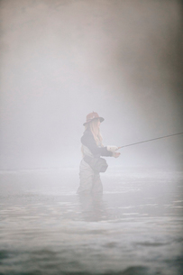 A woman fisherman fly fishing, standing in waders in thigh deep water.の写真素材 [FYI02858355]