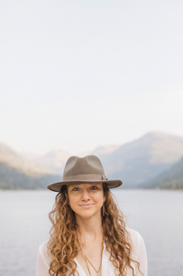 A woman in a wide brimmed hat by a mountain lake.の写真素材 [FYI02858362]