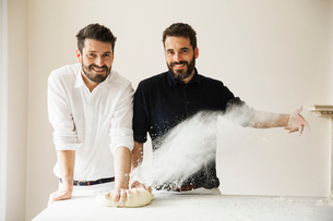 Two bakers standing at a table, kneading bread dough, dusting it with flour.の写真素材 [FYI02858363]