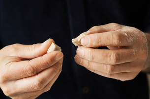 Close up of a baker holding pieces of fresh yeast in his hands.の写真素材 [FYI02858366]