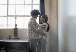 Loft living. A couple facing each other embracing.の写真素材 [FYI02858367]