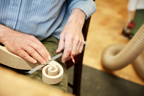 A violin maker using a ruler to measure the curled scroll of the violin headstock.の写真素材 [FYI02858369]