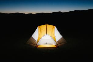 Illuminated camping tent in vast desert at dusk, Black Rock Desert, Nevadaの写真素材 [FYI02858374]