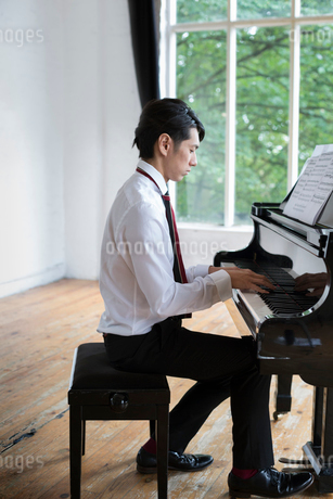 Young man playing on a grand piano in a rehearsal studio.の写真素材 [FYI02858383]