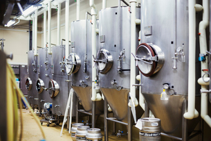 Row of large metal beer tanks in a brewery.の写真素材 [FYI02858384]