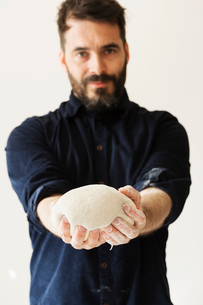 Baker holding a portion of bread dough shaped into a ball.の写真素材 [FYI02858388]