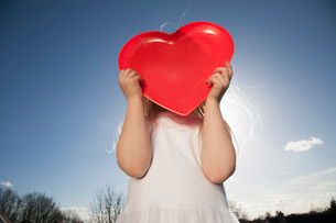 A child holding a red heart shape.の写真素材 [FYI02858404]