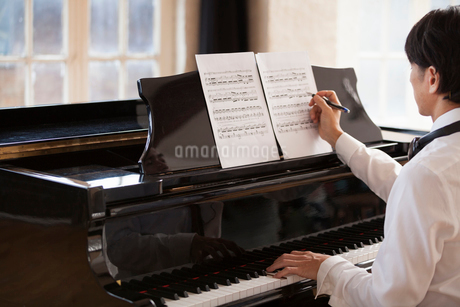 Young man sitting at a grand piano in a rehearsal studio, annotating sheet music.の写真素材 [FYI02858406]