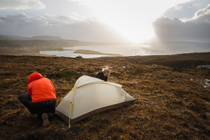 Two men holding and putting up a small tent in open space. Wild camping.の写真素材 [FYI02858407]