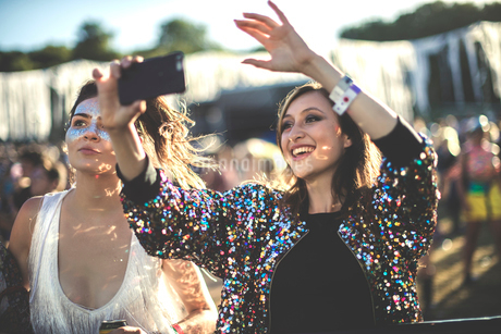 Young smiling woman at a summer music festival wearing multi-coloured sequinned jacket, taking pictuの写真素材 [FYI02858417]