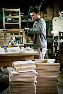 A man working in a furniture maker's workshop assembling a chair.の写真素材 [FYI02858419]