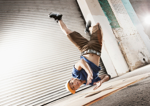 A young man upside down in mid air, break dancing doing a dive move on his shoulder, looking at theの写真素材 [FYI02858437]