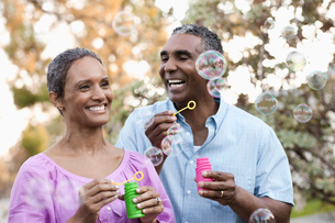 A mature couple, man and woman blowing bubbles celebrating an occasion outdoors.の写真素材 [FYI02858441]