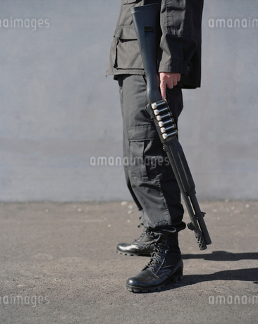 Cropped view of man in special forces, holding high powered shotgunの写真素材 [FYI02858468]