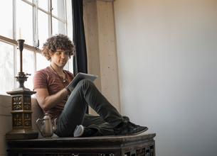 Loft living. A man sitting by a window using a digital tablet.の写真素材 [FYI02858471]