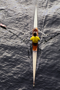A man sculling in a single scull rowing boat, on the water.  Overhead view.の写真素材 [FYI02858475]