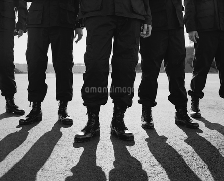 Low angle view of row of men wearing military uniforms, casting shadowsの写真素材 [FYI02858479]