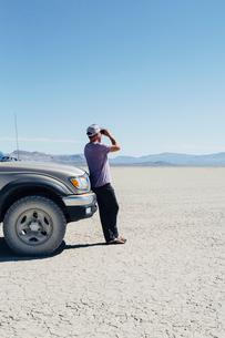 Man standing on vast desert, looking through binoculars and leaning against truck, Black Rock Desertの写真素材 [FYI02858481]