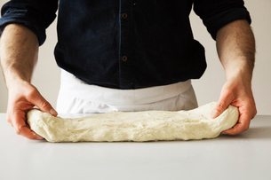 Close up of a baker kneading bread dough.の写真素材 [FYI02858499]