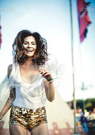 Young woman at a summer music festival wearing golden sequinned hot pants, face painted, smiling atの写真素材 [FYI02858504]