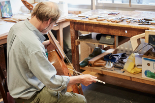 A violin maker in his workshop playing an instrument with a bow, tuning and finishing.の写真素材 [FYI02858506]