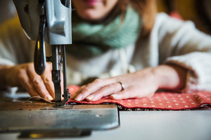 Upholstery workshop. A woman seated working with an industrial sewing machine, stitching fabric.の写真素材 [FYI02858511]