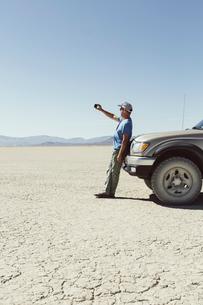 Man leaving against truck in desert, using smart phone, Black Rock Desert, Nevadaの写真素材 [FYI02858513]