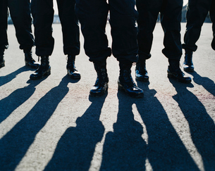 Low angle view of row of men wearing military uniforms, casting shadowsの写真素材 [FYI02858515]