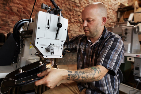 A leather worker, craftsman using an industrial sewing machine on leather material, making a bag.の写真素材 [FYI02858518]