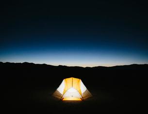 Illuminated camping tent in vast desert at dusk, Black Rock Desert, Nevadaの写真素材 [FYI02858529]