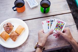 Close up of a man sitting at a table, holding playing cards.の写真素材 [FYI02858546]