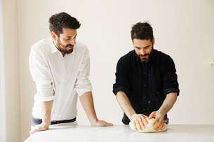 Two bakers standing at a table, kneading bread dough.の写真素材 [FYI02858558]