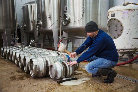 Man kneeling and hammering in a peg into a metal beer keg. Large fermentation tanks.の写真素材 [FYI02858560]