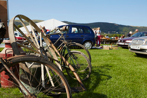 Selection of vintage bicycles, wheel rim and an old milk churn for sale at a flea market event.の写真素材 [FYI02858567]