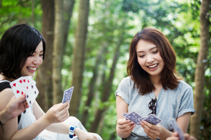 Two young women sitting in a forest, playing cards.の写真素材 [FYI02858568]