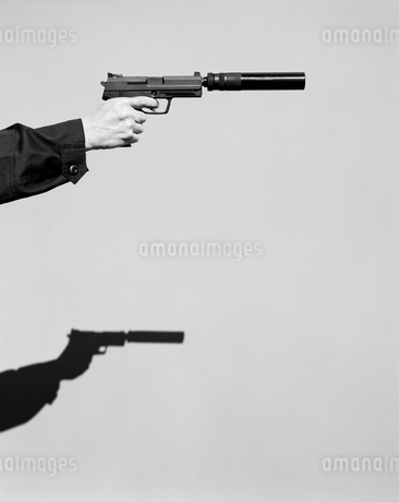 Detail of man aiming high powered hand gun with silencerの写真素材 [FYI02858573]