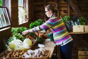 A woman handling produce in a farm shop.の写真素材 [FYI02858575]