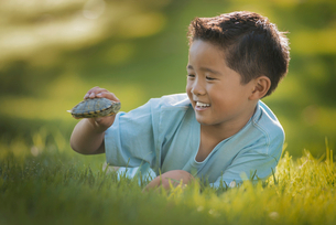 A boy lying on the grass holding a small terrapin or turtle.の写真素材 [FYI02858582]