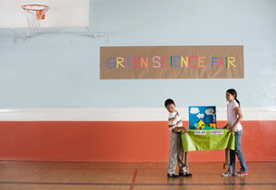 A boy and girl carrying a table with a presentation on solar power, at a Green Science Fair event.の写真素材 [FYI02858583]