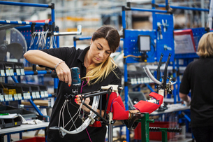 Female skilled factory worker assembling a bicycle in a factory working on the frame and wheels.の写真素材 [FYI02858586]