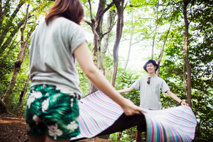 Young woman and man standing in a forest, holding a picnic rug.の写真素材 [FYI02858588]