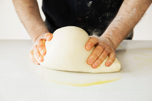 Close up of a baker kneading and shaping a large bread dough.の写真素材 [FYI02858589]