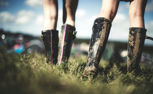 Low section rear view of two young women at a summer music festival wearing muddy Wellington boots.の写真素材 [FYI02858592]