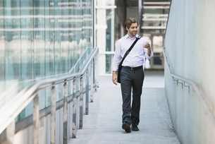 A man carrying a computer bag with a strap across his chest on along a city walkway.の写真素材 [FYI02858596]