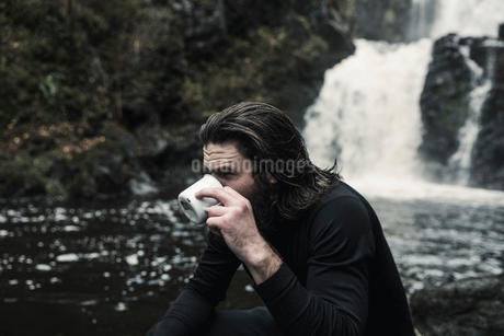 Wild camping. A man drinking from a cup by a fast flowing stream.の写真素材 [FYI02858599]