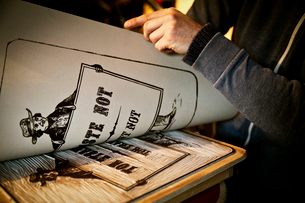 A sign writer lifting a sheet of imprinted card off a cut-out linoleum surface, a woodcut.の写真素材 [FYI02858607]