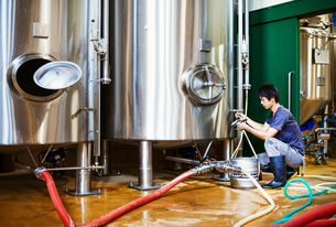 Man working in a brewery, kneeling beside a metal beer tank.の写真素材 [FYI02858622]