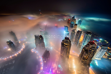 Aerial view of cityscape with illuminated skyscrapers above the clouds in Dubai, United Arab Emirateの写真素材 [FYI02858631]
