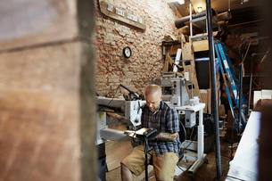 A leather worker, craftsman using an industrial sewing machine on leather material ion his workshop.の写真素材 [FYI02858635]