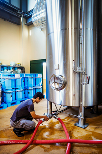Man working in a brewery, connecting hoses to a metal beer tank.の写真素材 [FYI02858651]